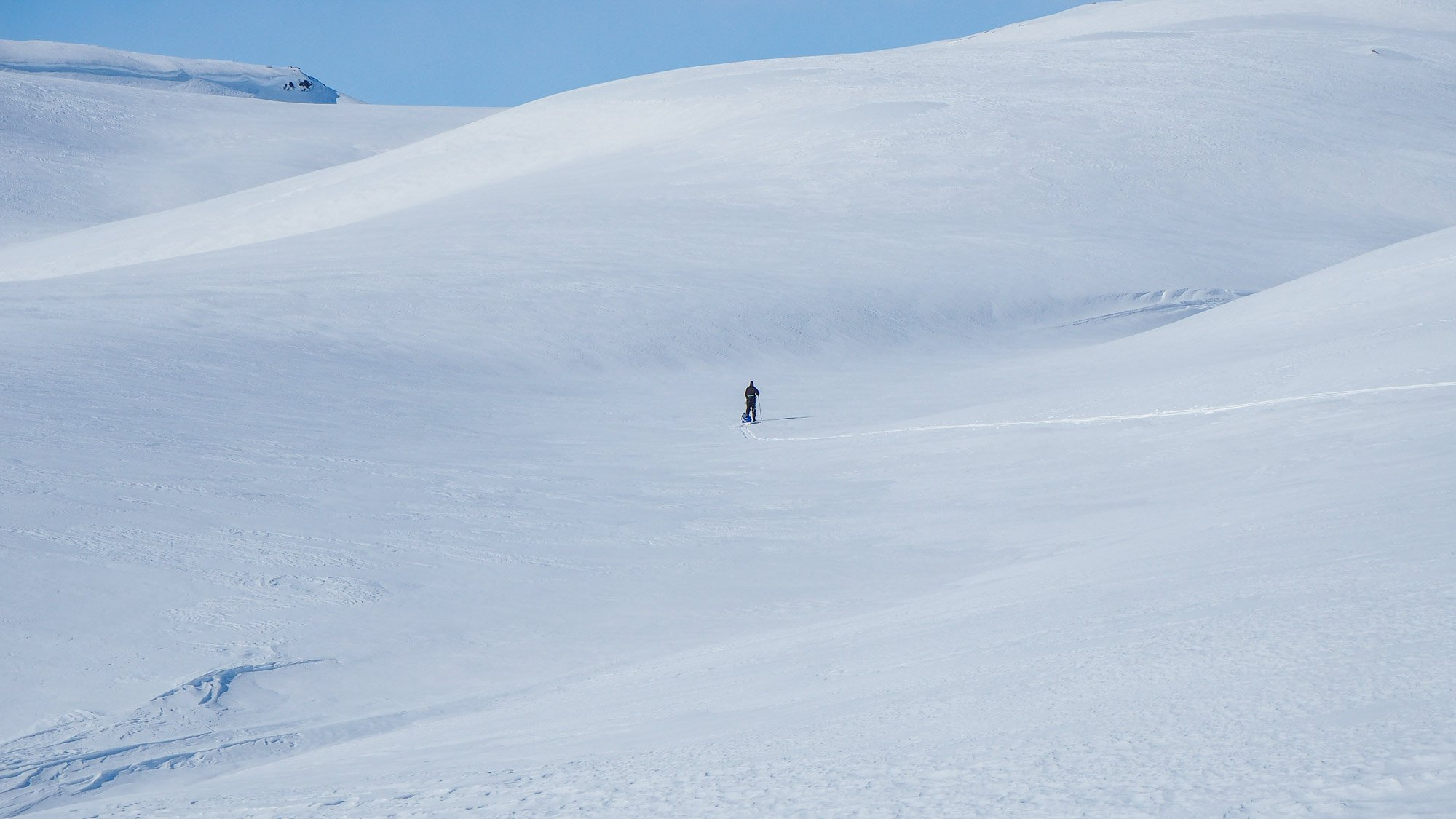 Yksinäinen pieni hahmo hiihtää lumierämaassa.