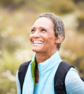smiling senior woman with backpack hiking outdoors