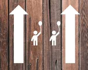 Wooden boards with two parallel arrows with icons of kids in between them to signify parallel parenting.