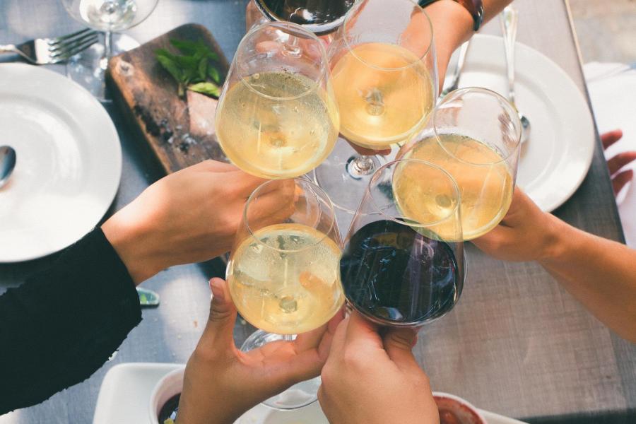 Des amis trinquent avec du vin blanc et du vin rouge