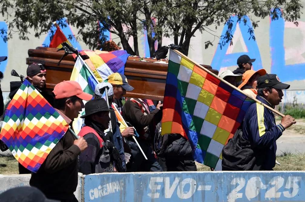 Manifestantes levam corpo de morto em protesto em El Alto e bandeiras wiphala durante ato desta quinta-feira (21) — Foto: Aizar Raldes/AFP