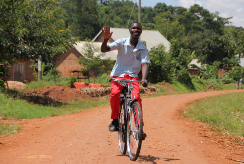 A teenage boy rides a bicycle along a road in Uganda. He is waving at the camera.