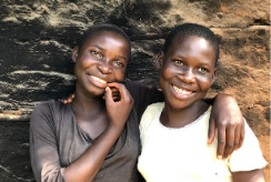 Twins sisters stand outside their home in Uganda