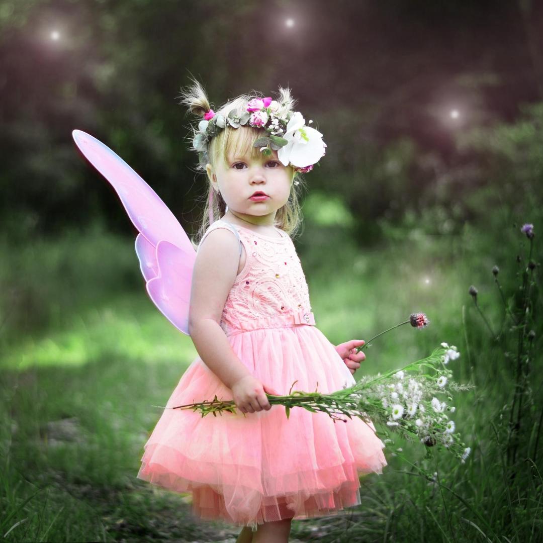 Little girl dressed as a fairy, in a garden.