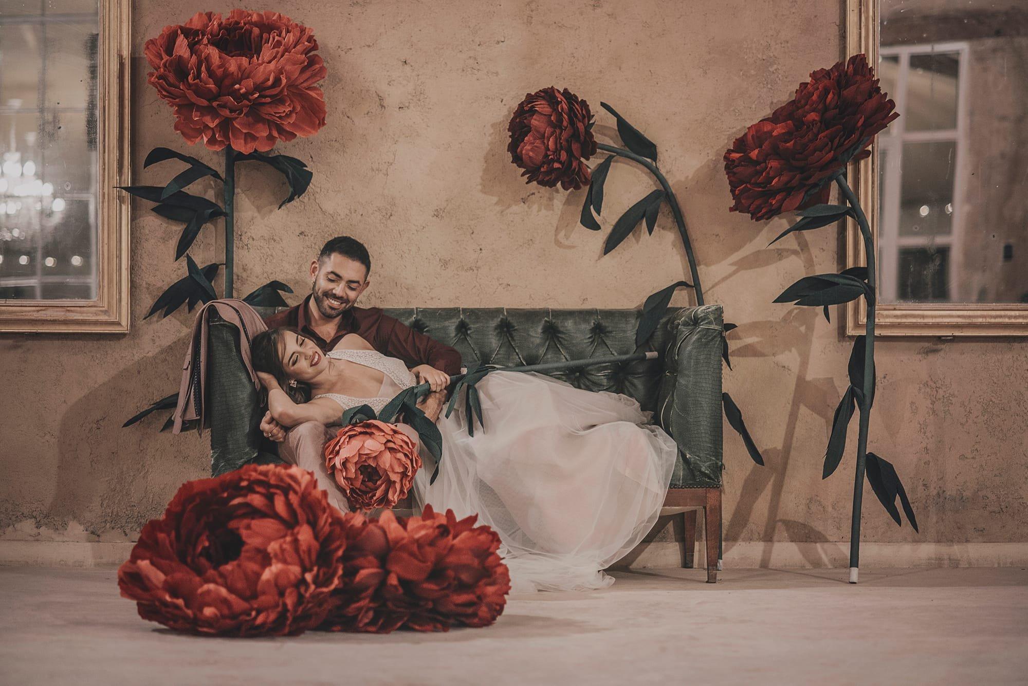 Mariés enlacé au château de Roquelune avec des pivoines rouges géantes