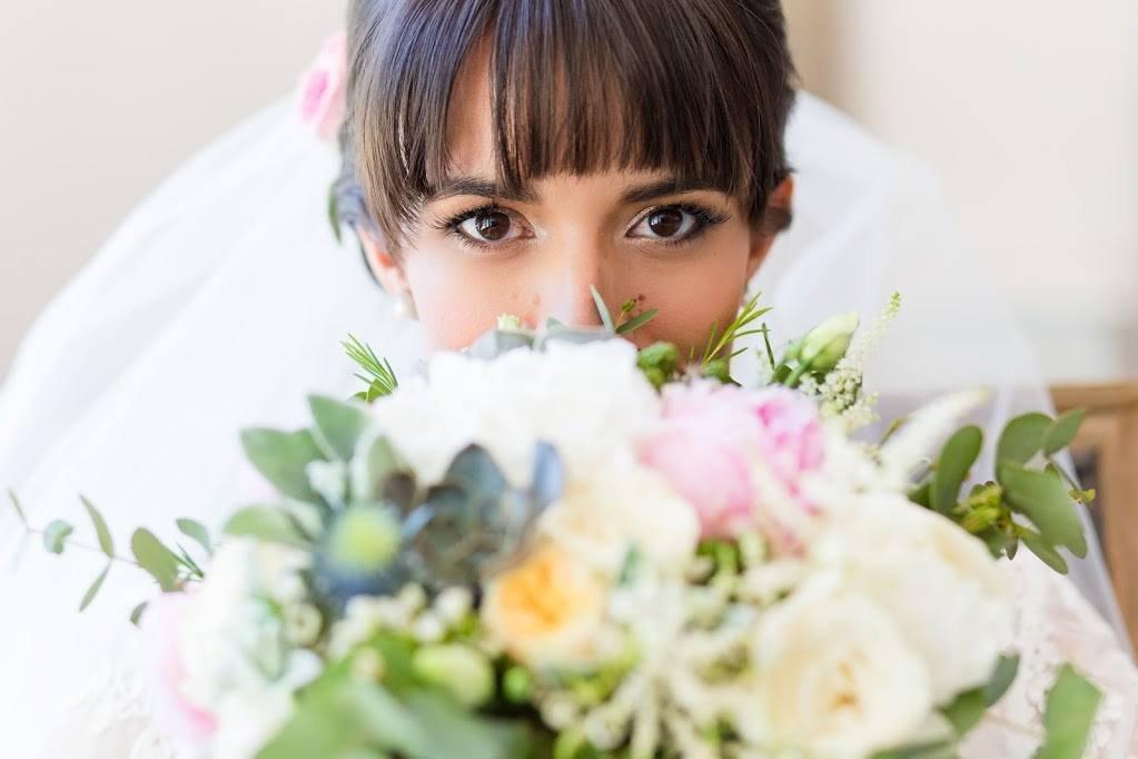 Mariée maquillée avec des yeux en amande et un bouquet de fleurs de mariée romantique