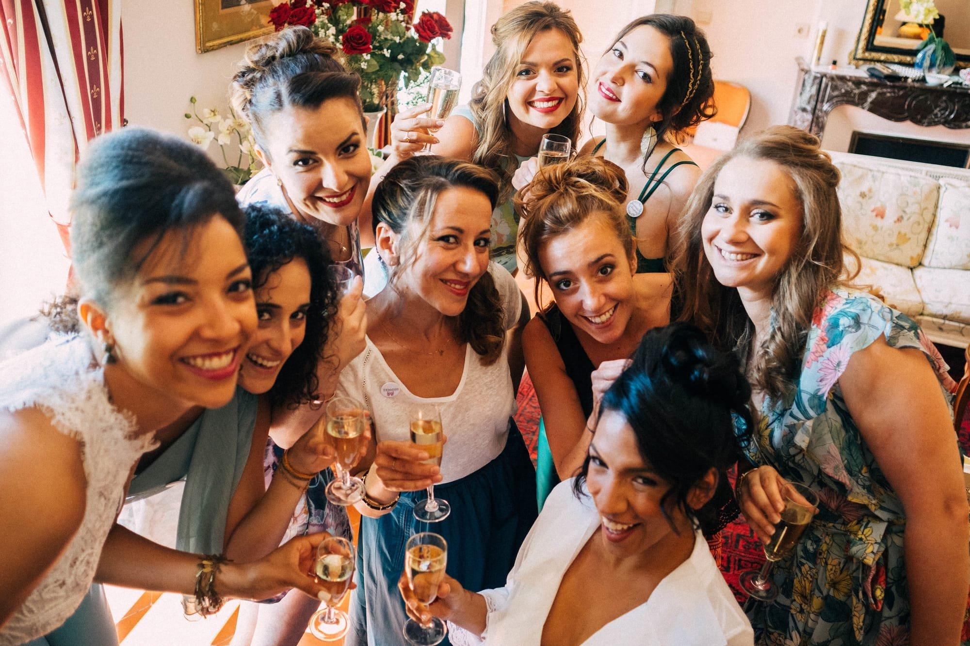 Mariée avec ses demoiselles d'honneur buvant une coupe de champagne