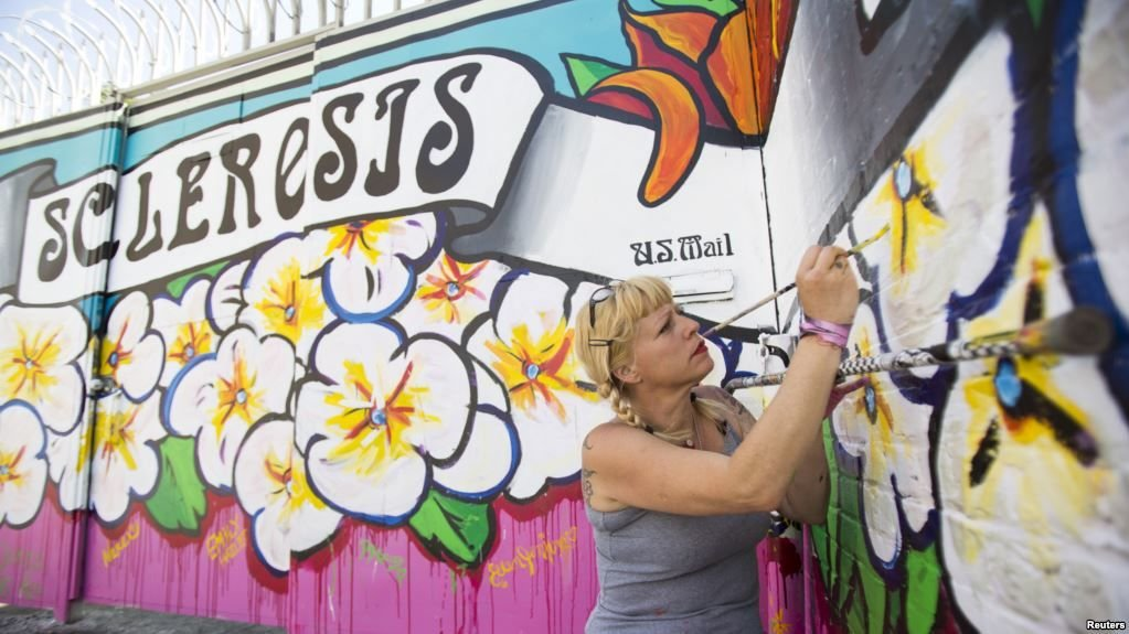FILE - Street artist Lydia Emily Archibald, who was diagnosed with multiple sclerosis in 2012, touches up her mural aimed at raising awareness about the disease in Los Angeles, April 9, 2015.